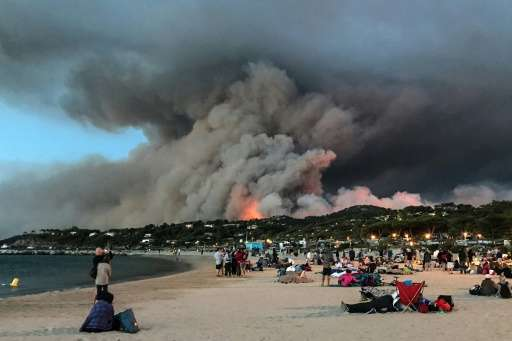 Evacuated people who took refuge on the beach look at a fire burning the forest in Bormes-les-Mimosas on France's Mediterranean