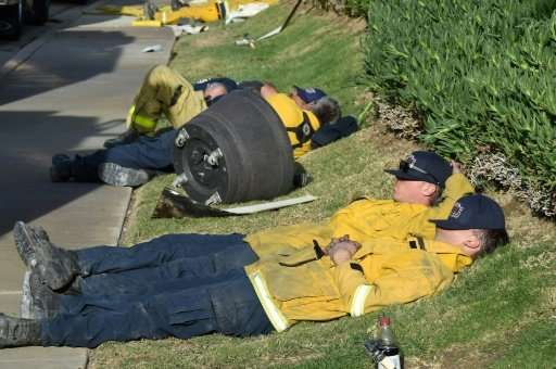 Exhausted firefighters have their first rest in over 20 hours since starting to fight the Lilac Fire in Bonsall, California