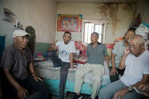 Farmer Wang Enlin (2nd L) sits in his house with fellow environmental activists who have taken on a subsidiary of China's larges