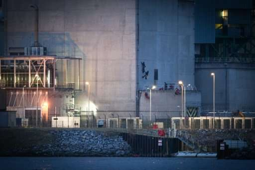 Four Greenpeace activists scaled one of the buildings at the nuclear plant and set off flares