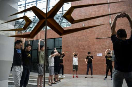 Gamers from various eSports teams take a break to perform some physical exercise during training for the League of Legends World