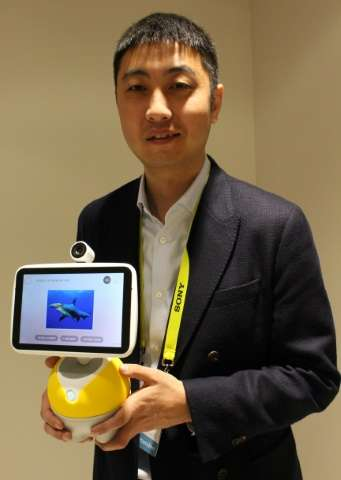 Jing Kun, GM of operating system DuerOS, holds Baidu's new 'Little Fish' voice controlled virtual valet which is powered by Duer
