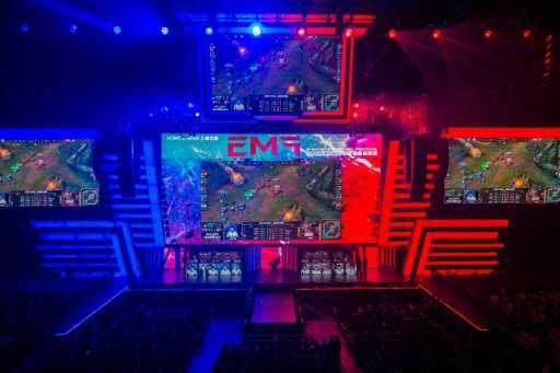 Members of team Hong Kong, Taiwan and Macau (centre R) and team Europe (centre L) compete on stage during the League of Legends