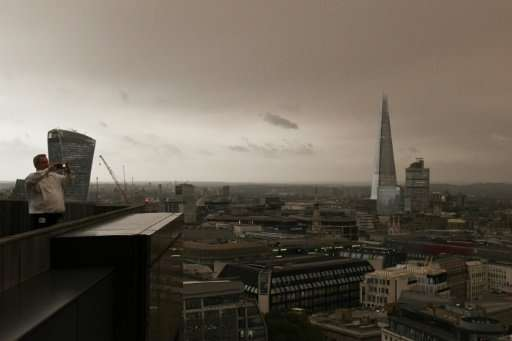Office workers took time out to photograph the darkened sky over London, caused by warm air and dust swept up by storm Ophelia.