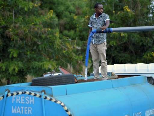 Patrick Kilonzo fills a hired bowser water tanker before embarking on a 70 kilometre journey to deliver the water to thirsty wil
