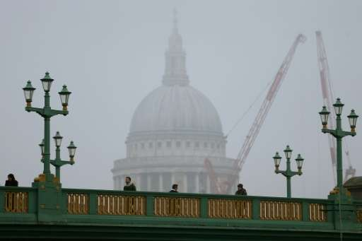 Pedestrians walk through the fog as they cross Southwark Bridge in London as St Paul's Cathedral looms in the background on Janu