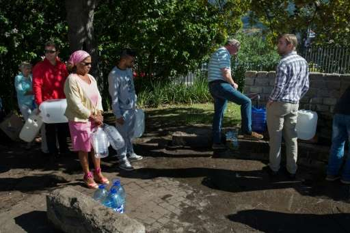 People queue up to collect drinking water from taps that are fed by a spring in Newlands on May 15, 2017, in Cape Town