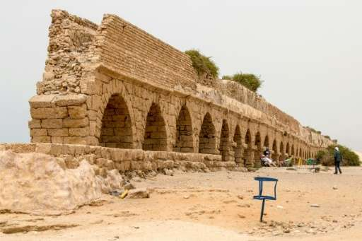 People sit next to an ancient aqueduct in the Roman-era city of Caesarea which is set for renovation as part of a multi-million-