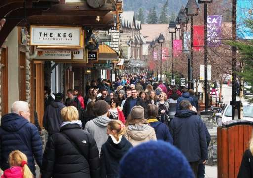 People stroll through the town of Banff inside Banff National Park, Alberta. Canada's national parks contribute Can$1.5 billion