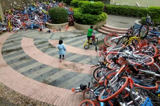 Rented bicycles from bike-sharing firms are stacked near the entrance of Xiashan park in Shenzhen, on January 16, 2017