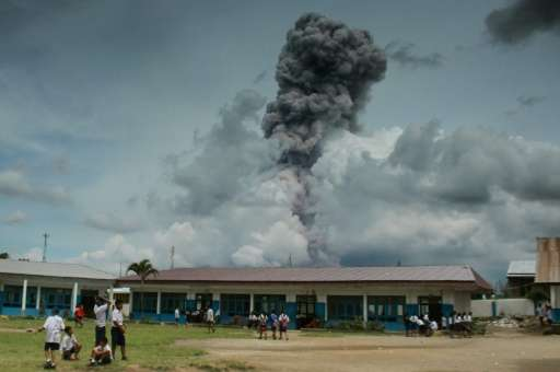 School pupils play on Indonesia's Sumatra island as Mount Sinabung, a highly active volcano, spews thick smoke