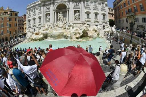 Sightseers shelter from the sun under an umbrella in front of Trevi fountain in Rome as temperatures reached more than 40 degree