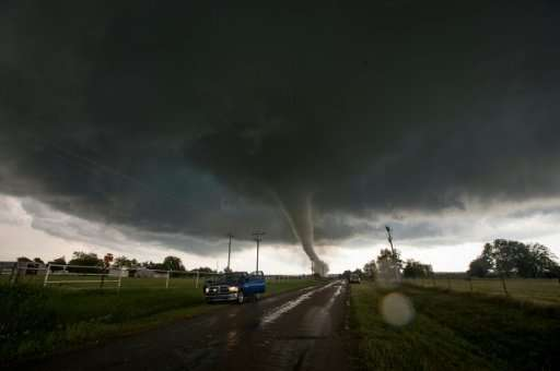 Vehicles stop on the side of a road as a tornado rips through a residential area in Oklahoma