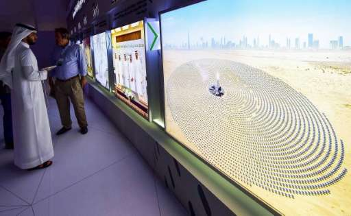 Visitors look at screens displaying images of the Mohammed bin Rashid Al-Maktoum Solar Park on March 20, 2017, at the solar plan