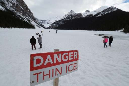 Visitors walk on frozen Lake Louise at Banff National Park in Alberta. The government has increased funding for Parks Canada but
