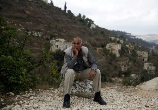 Yacoub Odeh, a 77-year-old Palestinian, sits by old houses in the ghost village of Lifta, whose Palestinian inhabitants fled dur