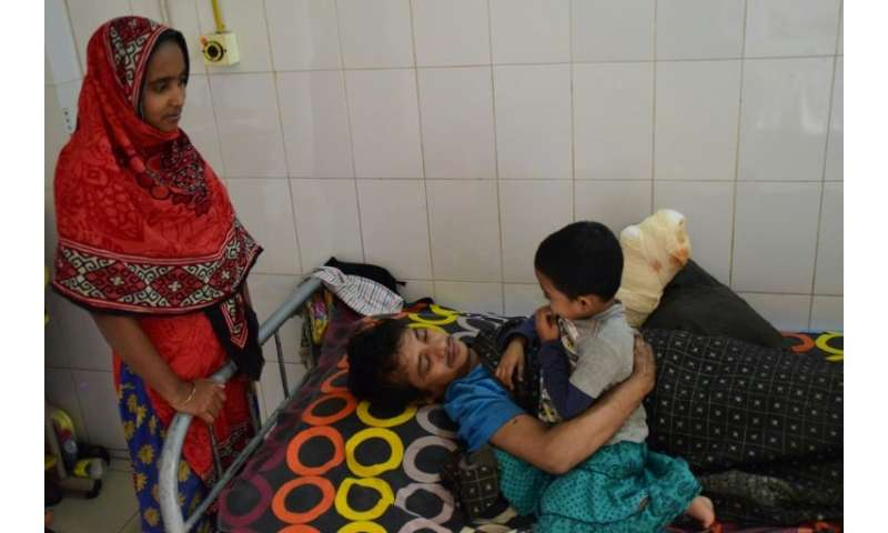 Abul Bajandar, with his family at a Dhaka hospital, worries about money and how he will pay for his daughter's education