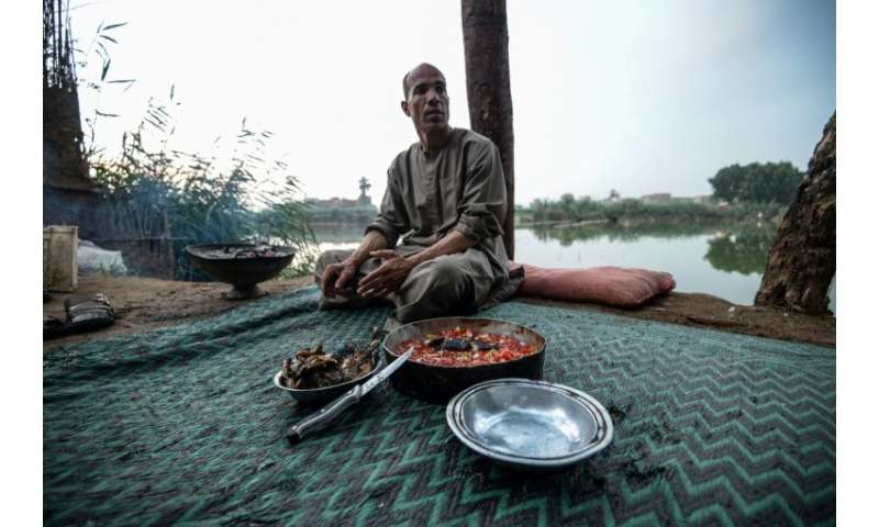 An Egyptian fisherman prepares a meal next to the Pharaonic Sea
