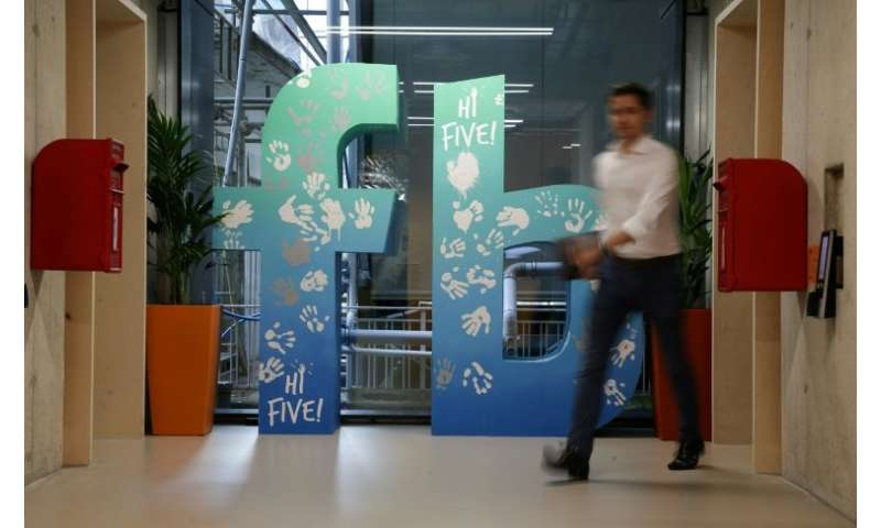 An employee walks past a Facebook logo at its new London headquarters