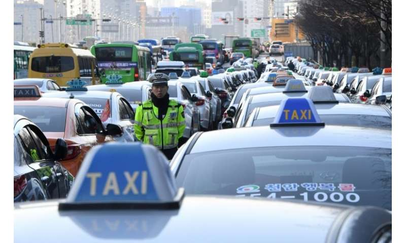An estimated 50,000 taxi drivers protested in Seoul to call for a car-pooling app to be banned