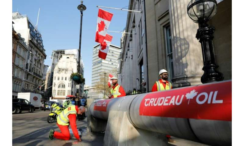 Demonstrators use a mock oil pipeline to block the entrance to the Canadian Embassy in central London as they protest against th