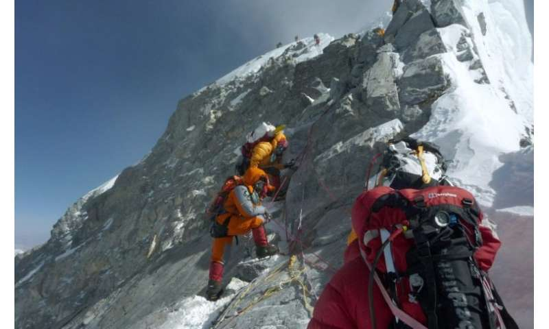 Mountaineers walk past the Hillary Step while pushing for the summit of Mount Everest on the south face from Nepal, in a file ph