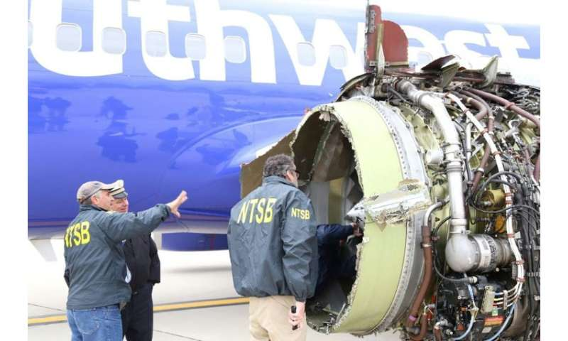 National Transportation Safety Board investigators examine damage to a Southwest Airlines plane that suffered catastrophic engin