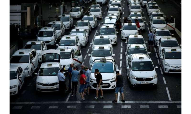 Taxi drivers blocked a major avenue in Madrid on Tuesday as a strike against Uber-style ride hailing services was set to enter a