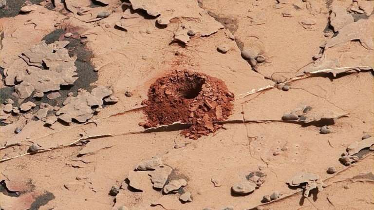This NASA image shows a 2-inch-deep hole the rover Curiosity drilled on the Martian surface to extract rock samples in May 2018