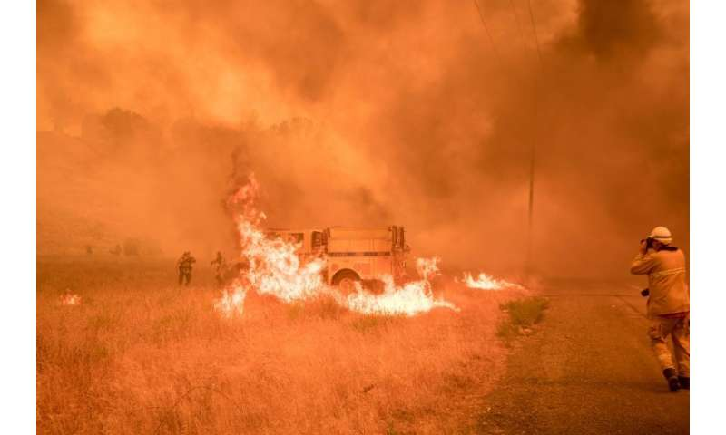 Firefighters scramble to control flames surrounding a fire truck as the Pawnee fire jumps across highway 20 near Clearlake Oaks,