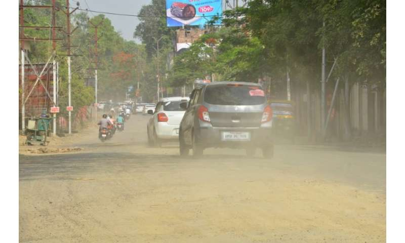 Indian commuters drive along a dusty road in Kanpur, judged to have the worst air pollution in a WHO global list of cities