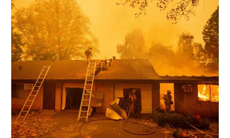 Firefighters battle flames at the Shadowbrook apartment complex in Paradise, north of Sacramento, California—the town has been r