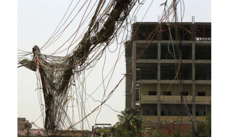A picture taken on July 26, 2018, shows loose wires coming from a generator in Baghdad installed to supplement the poor public p
