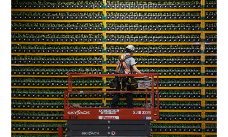 (FILES) In this file photo taken on March 19, 2018 A technician inspects the backside of bitcoin mining at Bitfarms in Saint Hya