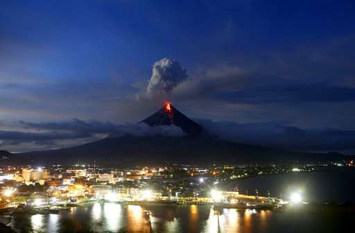 Lava spilling from Philippine volcano, ash coating land