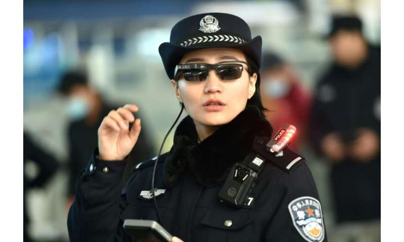 A Chinese police officer wears a pair of smartglasses with a facial recognition system at Zhengzhou East Railway Station in Zhen