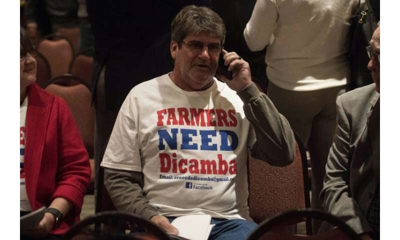 """A farmer wearing a T-shirt reading """"Farmers Need Dicamba"""" speaks on his phone during a break at a public hearing of th"""