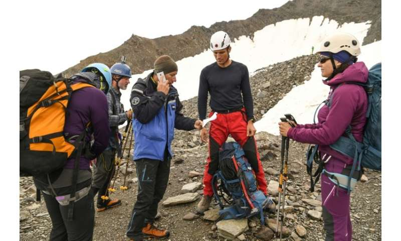 A French gendarme confirms by telephone a hut reservation for a group of climbers before allowing them to start toward the Mont