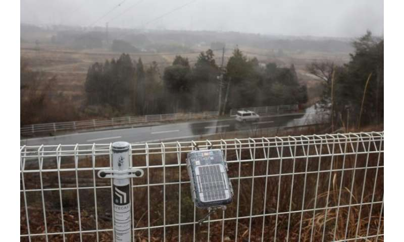 A geiger counter operated by the Safecast group is attached to a fence near the stricken Dai-ichi power plant