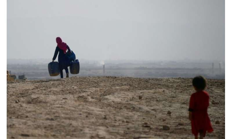 A girl carries containers to collect water on the outskirts of Mazar-i-Sharif in northern Afghanistan, where a lack of snow and