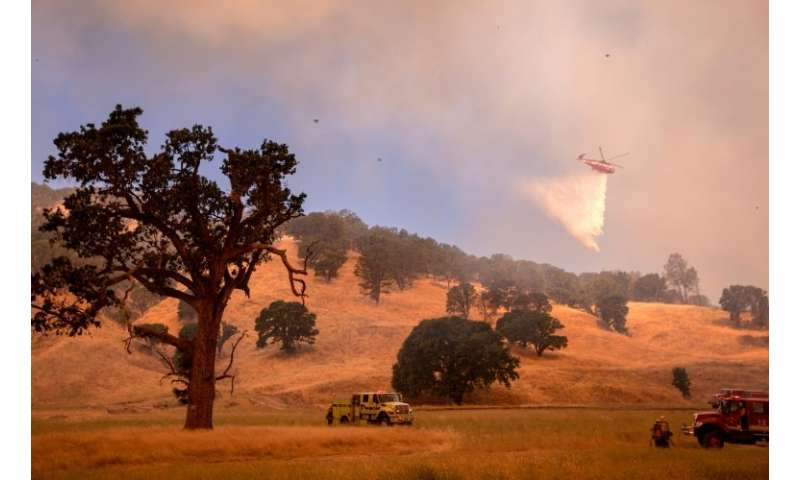 A helicopter drops water on a hillside as firefighters scramble to get control as flames from the Pawnee fire near Clearlake Oak