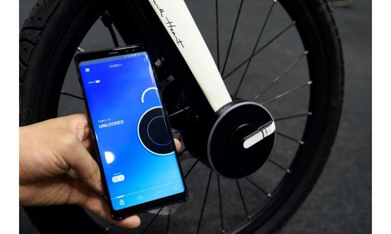 A host holds a mobile phone used to lock a Bisecu Smart Bike Lock on a bycicle at the Mobile World Congress (MWC), the world's b