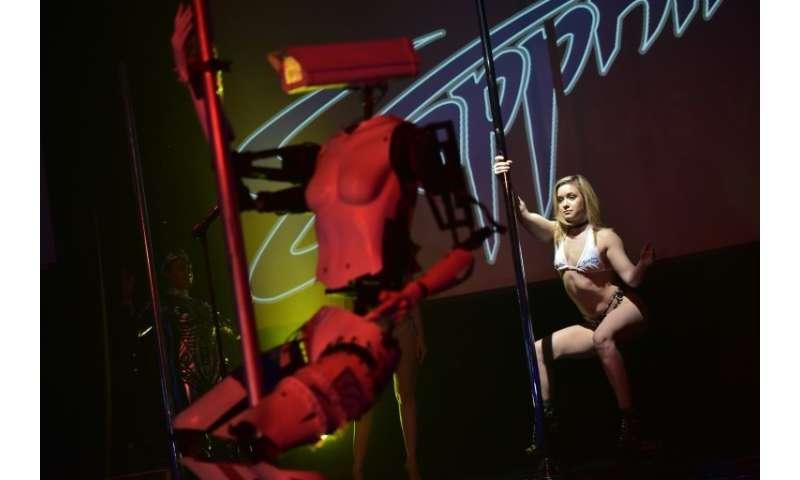 A human dancer performs next to a stripper robot at the Sapphire Gentlemen's Club in Las Vegas