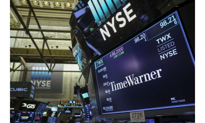 A logo and trading information for Time Warner is seen on a monitor on the floor of the New York Stock Exchange (NYSE), on June