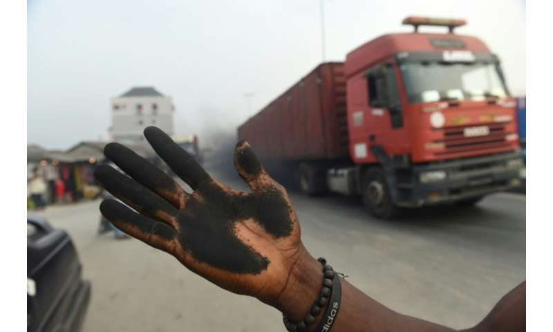 A man holds out his soot covered hand to illustrate how much soot covered the bonnet of his car in Port Harcourt