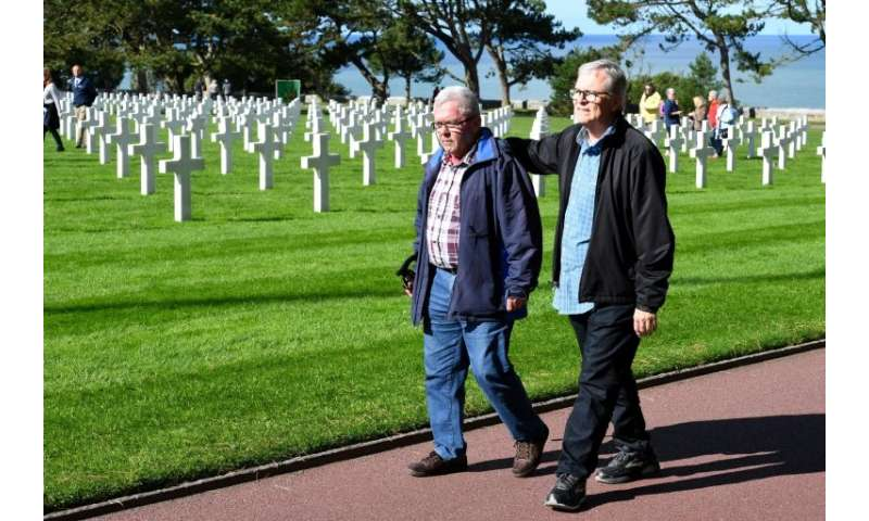 Andre Gantois and Allen Henderson, seen at the Normandy American Cemetery and Memorial, had the same GI father who landed near