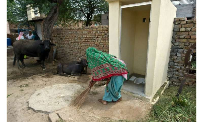 An Indian villager sweeps around a new toilet built as part of a public health drive launched by Prime Minister Narendra Modi