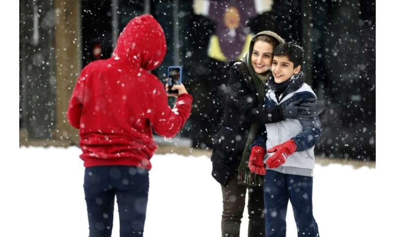 An Iranian woman and a child pose for a photograph during a snowstorm in the capital Tehran on January 28, 2018
