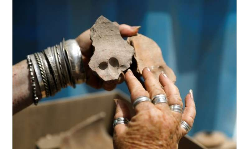 An Israel Antiquities Authority archaeologist shows shows pottery shreds with finger prints on them from the Byzantine time foun