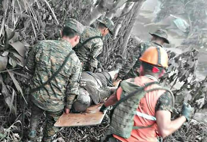 A picture released by the Guatemalan National Army shows soldiers evacuating a victim of the eruption of Guatemala's Fuego volca